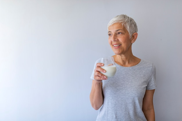 Middle age woman drinking a glass of fresh milk with a happy face standing and smiling with a confident smile showing teeth. Premium Photo