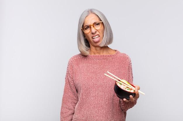 中年女性は嫌悪感とイライラを感じ、孤立した舌を突き出します Premium写真