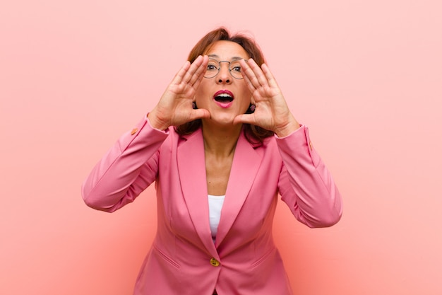 Middle age woman feeling happy, excited and positive, giving a big shout out with hands next to mouth, calling out  pink wall Premium Photo