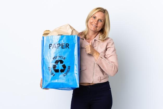 親指を立てるジェスチャーを与える白で隔離のリサイクルする紙でいっぱいのリサイクルバッグを保持している中年女性 Premium写真