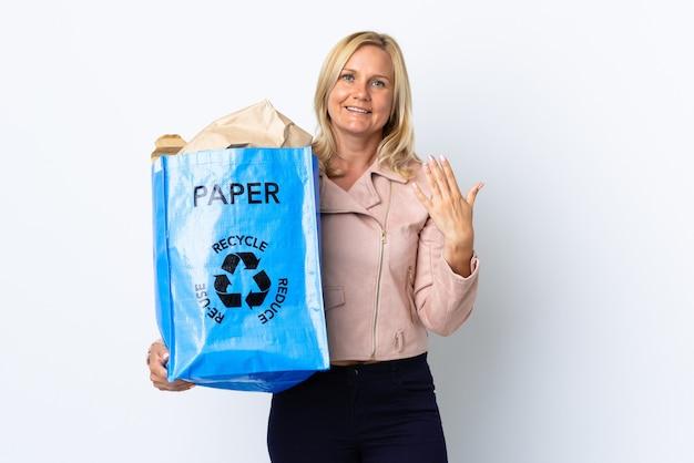 手に持って来るように誘う白で隔離されたリサイクルする紙でいっぱいのリサイクルバッグを持っている中年女性。あなたが来て幸せ Premium写真
