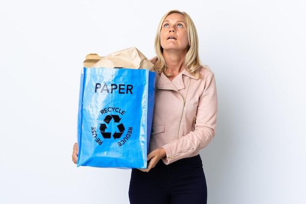 紙でいっぱいのリサイクルバッグを持っている中年女性が見上げると驚きの表情で白で隔離のリサイクル Premium写真