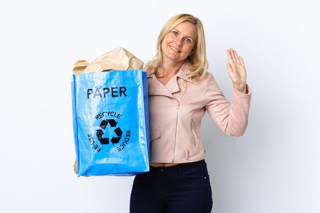紙でいっぱいのリサイクルバッグを持っている中年女性が幸せな表情で手で敬礼する白い上に隔離されたリサイクル Premium写真