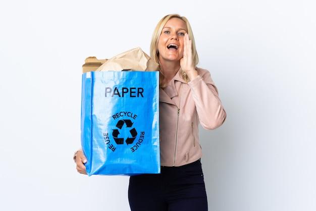 口を大きく開いて白い叫びで隔離されたリサイクルする紙でいっぱいのリサイクルバッグを保持している中年女性 Premium写真