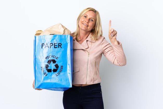 紙でいっぱいのリサイクルバッグを持ってリサイクルする中年の女性は、最高の兆候を示して指を持ち上げて白で隔離 Premium写真