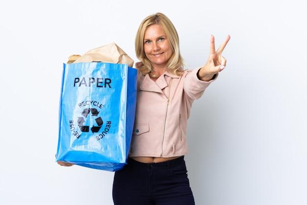 紙でいっぱいのリサイクルバッグを持っている中年の女性は、白い笑顔と勝利のサインを示して分離されたリサイクルする Premium写真