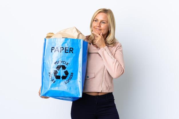 横を向いて笑顔で白い壁に隔離されたリサイクルする紙でいっぱいのリサイクルバッグを持っている中年女性 Premium写真