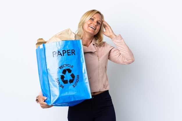 たくさん笑って白い壁に隔離されたリサイクルする紙でいっぱいのリサイクルバッグを保持している中年女性 Premium写真