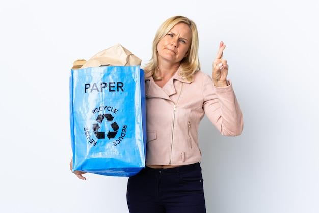 紙でいっぱいのリサイクルバッグを持っている中年の女性は、指を交差させて、最高の願いを白で隔離してリサイクルします Premium写真