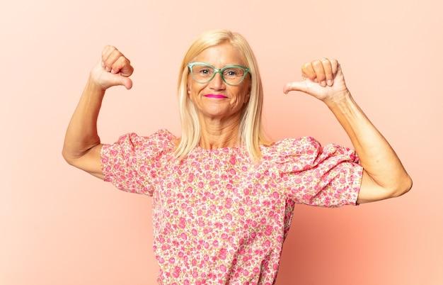 中年の女性は悲しみ、失望、または怒っているように見え、不一致で親指を下に見せています Premium写真