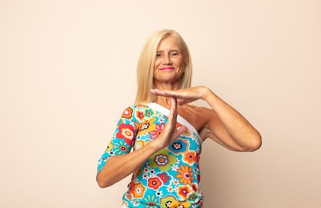 Женщина среднего возраста выглядит серьезной, суровой, сердитой и недовольной, делая знак тайм-аута Premium Фотографии