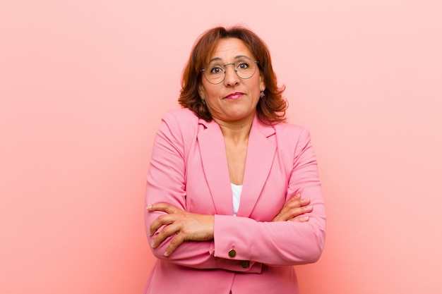 Middle age woman shrugging, feeling confused and uncertain, doubting with arms crossed and puzzled look against pink wall Premium Photo