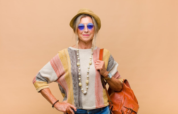 Middle age woman smiling happily with a hand on hip and confident, positive, proud and friendly attitude Premium Photo