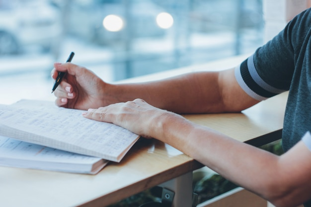 Middle-aged adult woman doing homework on the chinese language Premium Photo