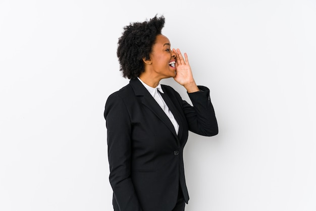 Middle aged african american business  woman against a white wall isolated shouting and holding palm near opened mouth. Premium Photo
