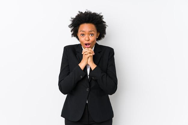 Афро-американская бизнес-леди средних лет на белом изолировала молящуюся на удачу, изумленно и открывая рот, смотрящую вперед. Premium Фотографии