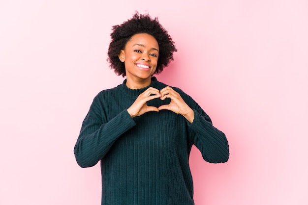 ピンクの表面に対して中年のアフリカ系アメリカ人の女性は、笑顔と手でハートの形を示しています。 Premium写真
