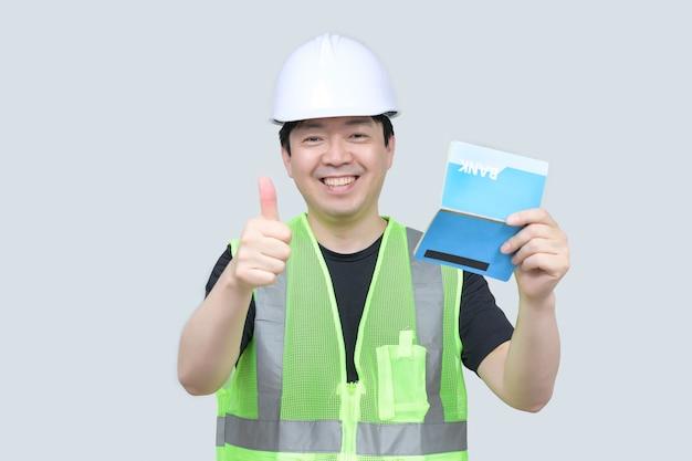 Азиатский инженер средних лет держит банковскую книжку Premium Фотографии