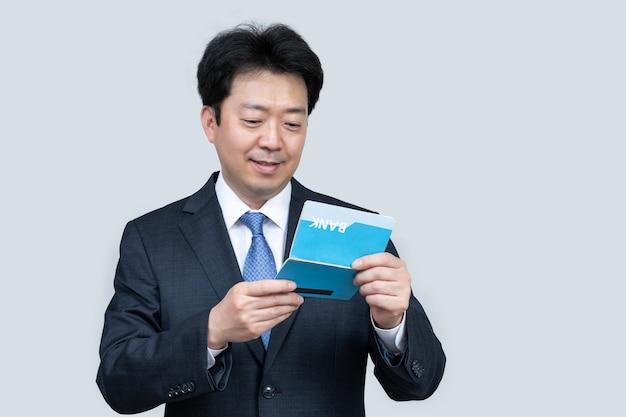 Азиатский мужчина средних лет держит банковскую книжку Premium Фотографии