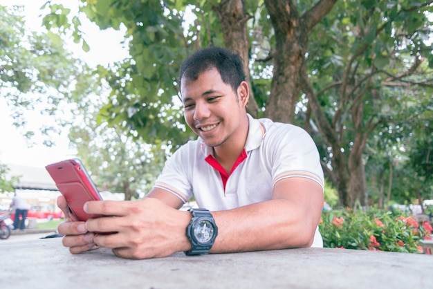 Middle-aged asian man using mobile phone on the table in the park near the evening time.he look happy moment. concept of relax people working mobile devices. Premium Photo
