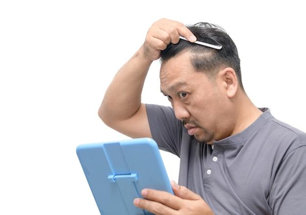 Азиатский мужчина средних лет беспокоится о выпадении волос или облысении и изолировании седых волос Premium Фотографии