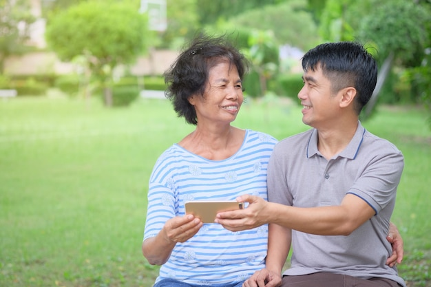 Middle-aged asian mother and son looking at each other and looking at a smartphone with a smile and being happy at the park is an impressive warmth Premium Photo
