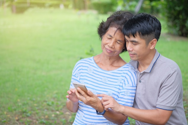 Middle-aged asian mother and son looking at a smartphone with a smile and being happy at the park is an impressive warmth Premium Photo