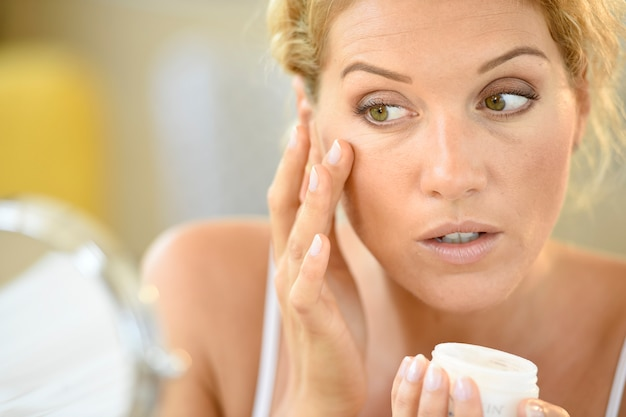 Middle-aged blond woman putting cosmetics on Premium Photo