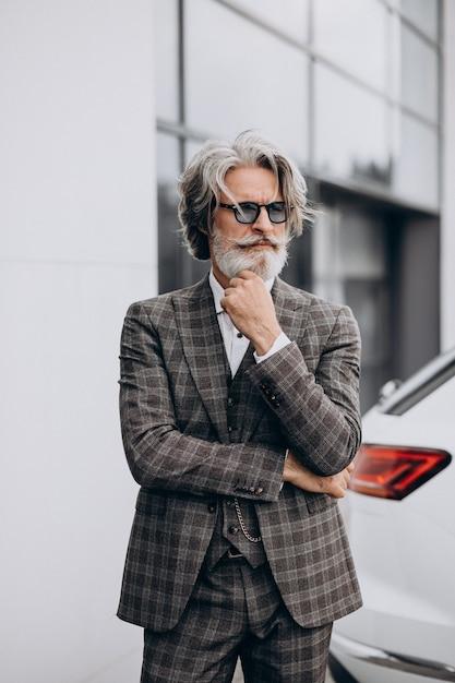 Uomo d'affari di mezza età in un salone di automobile Foto Gratuite