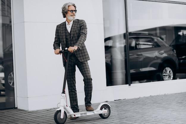 Uomo d'affari di mezza età in sella a uno scooter in un abito di classe Foto Gratuite