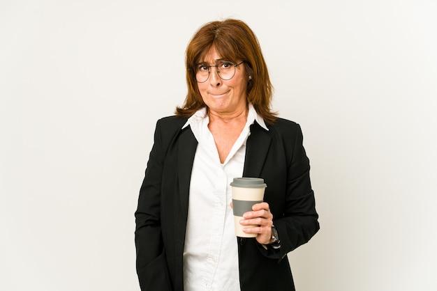 고립 된 테이크 아웃 커피를 들고 중간 나이 든된 비즈니스 여자는 혼란 스 러 워, 의심스럽고 확신을 느낍니다. 프리미엄 사진