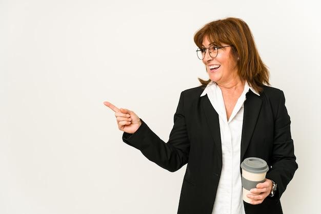 테이크 아웃 커피를 들고 중간 나이 든된 비즈니스 여자 절연 웃 고 옆으로 가리키는, 빈 공간에서 뭔가 보여주는. 프리미엄 사진