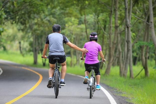 공원에서 자전거와 함께 운동을 편안 하 게 중간 나이 든된 부부 프리미엄 사진