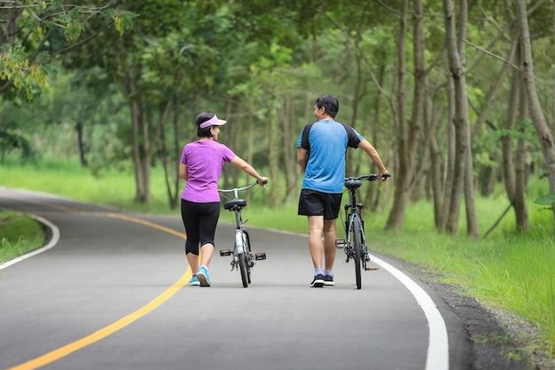 공원에서 자전거와 함께 운동을 편안 하 게 중간 세 커플 프리미엄 사진