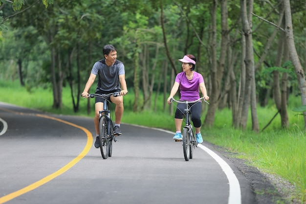 Middle aged couple relaxing exercise with bicycle in park Premium Photo
