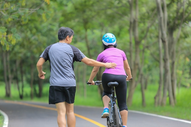 Middle aged couple walking with their bicycle in park Premium Photo