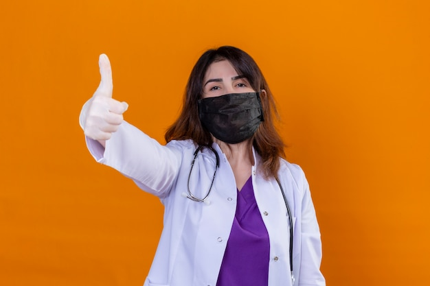 Middle aged doctor wearing white coat in black protective facial mask and with stethoscope positive and happy showing thumbs up over orange wall Free Photo