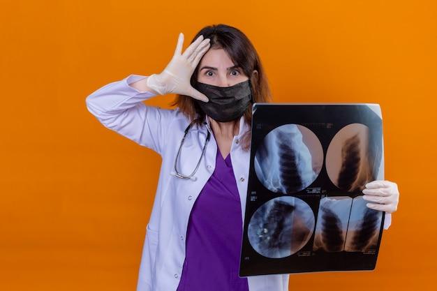 Доктор средних лет в белом халате в черной защитной маске для лица и со стетоскопом, держащим рентген легких, выглядящий удивленным с рукой возле головы над оранжевой стеной Бесплатные Фотографии