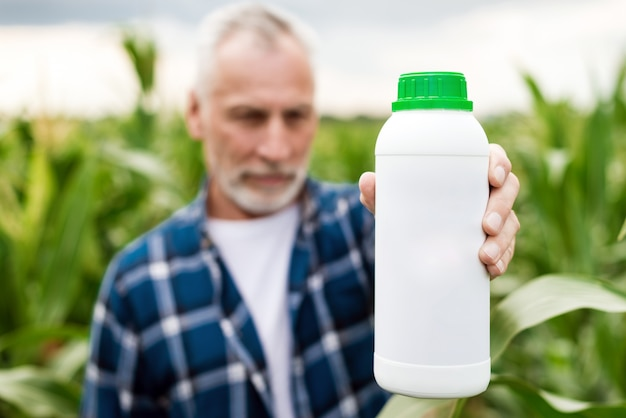 Middle aged farmer in a field showing a bottle with chemical  fertilizers. Premium Photo