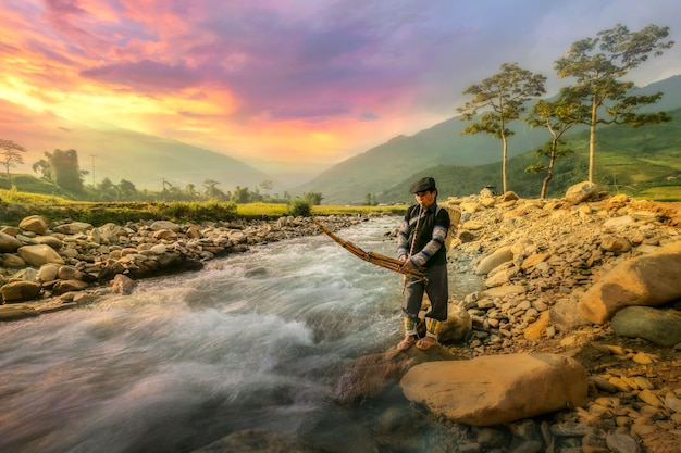 Middle aged farmer playing a musical instrument by the edge of the stream in the countryside in the north of vietnam Premium Photo