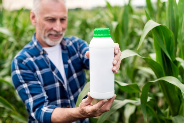 Middle aged farmer standing in a field looking on a  bottle with chemical fertilizers in his hands. Premium Photo
