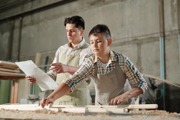 ワークショップで木製家具を組み立てる息子に青写真を読んでエプロンの中年の父 Premium写真