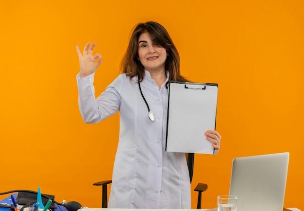 クリップボードを保持し、コピースペースを持つオレンジ色の壁にオーケージェスチャーを示すラップトップでラップトップで机の仕事の後ろに聴診器立って医療ローブを着て中年女性医師 無料写真