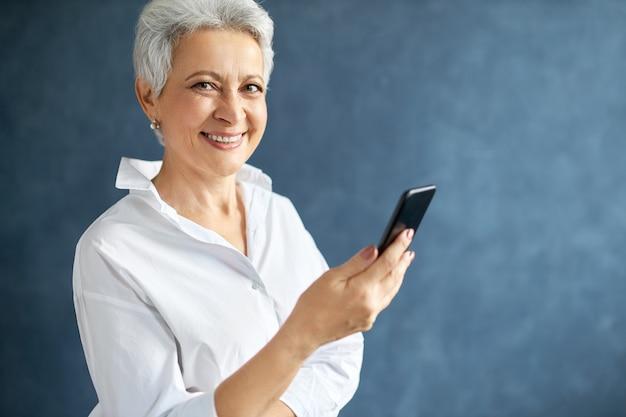 Imprenditrice di mezza età con capelli grigi corti che tiene il cellulare, effettua chiamate di lavoro, digita un messaggio di testo. Foto Gratuite