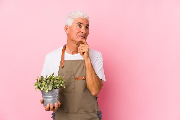 Мужчина-садовник средних лет изолированно смотрит в сторону с сомнительным и скептическим выражением лица. Premium Фотографии