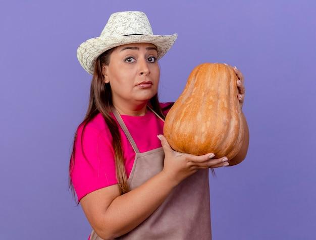 紫色の背景の上に立っている深刻な顔でカメラを見てカボチャを保持しているエプロンと帽子の中年庭師の女性 無料写真