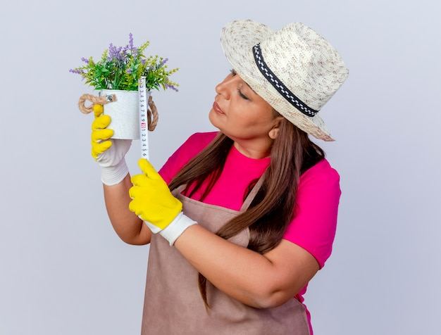앞치마와 고무 장갑을 끼고 고무 장갑을 끼고있는 중간 세 정원사 여자 테이프 측정으로 측정하는 화분을 들고 흰색 배경 위에 서있는 흥미 진진한 서 무료 사진