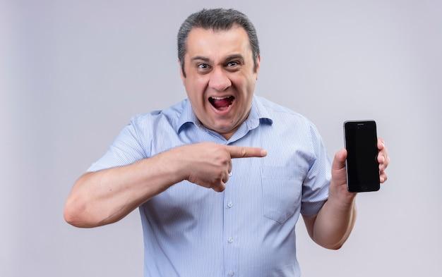 Uomo di mezza età in camicia a righe verticali blu tenendo la bocca aperta e indicando con il dito indice il suo telefono cellulare mentre si trova su uno sfondo bianco Foto Gratuite