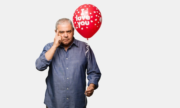 Middle aged man celebrating valentines day doing a concentration gesture Premium Photo