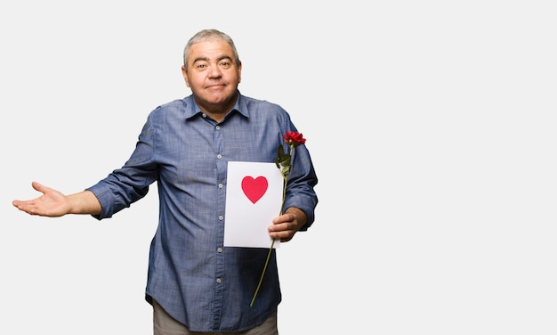 Middle aged man celebrating valentines day doubting and shrugging shoulders Premium Photo